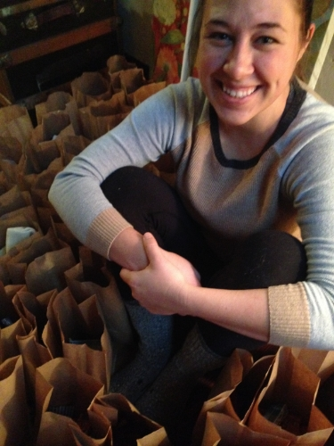 Emily Taylor, my right hand and fellow dedicated yogini of service, sits amidst the 100+ bags full of love in the puja room at the YogaFarm