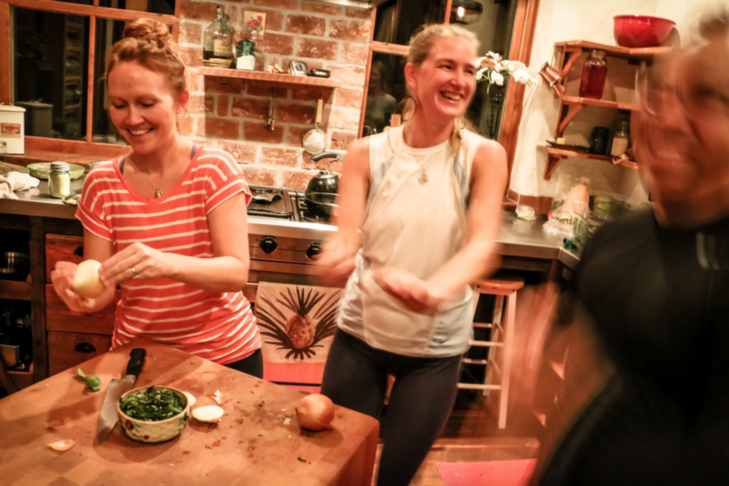 Retreat guests at the YogaFarm making dinner (and dancing)  in the kitchen [photo: Raku Loren]