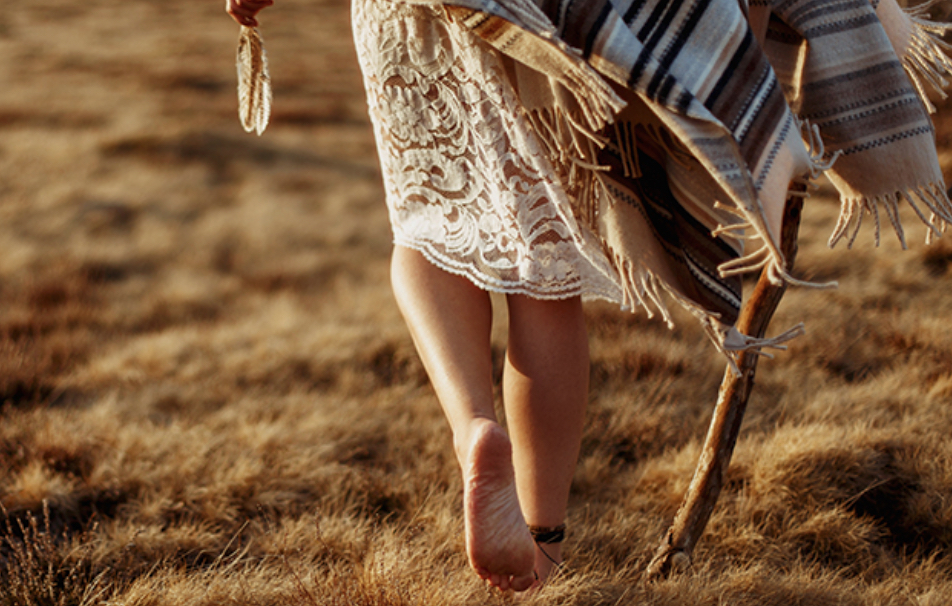 woman walking with staff & feather.jpg