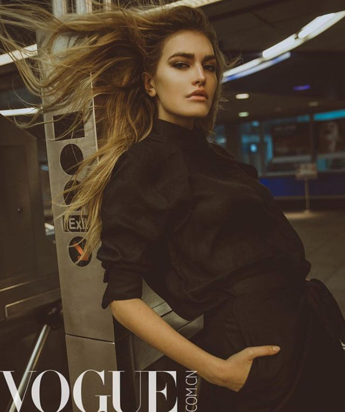 model leaning against NYC subway post in black shirt by Marine Penvern, Vogue magazine