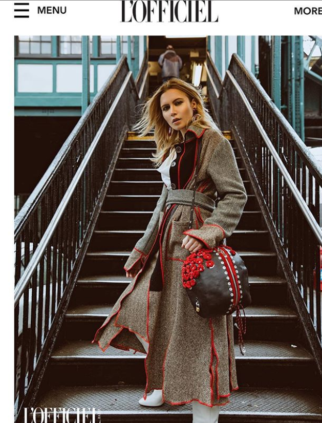 model in long gray coat with red piping by Marine Penvern, L'Officiel magazine; set on NYC subway stairs