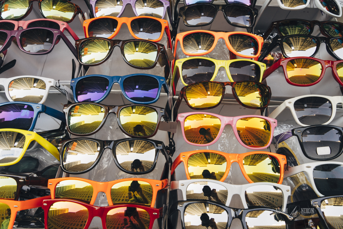 Street vendor display of colorful sunglasses with a reflection o