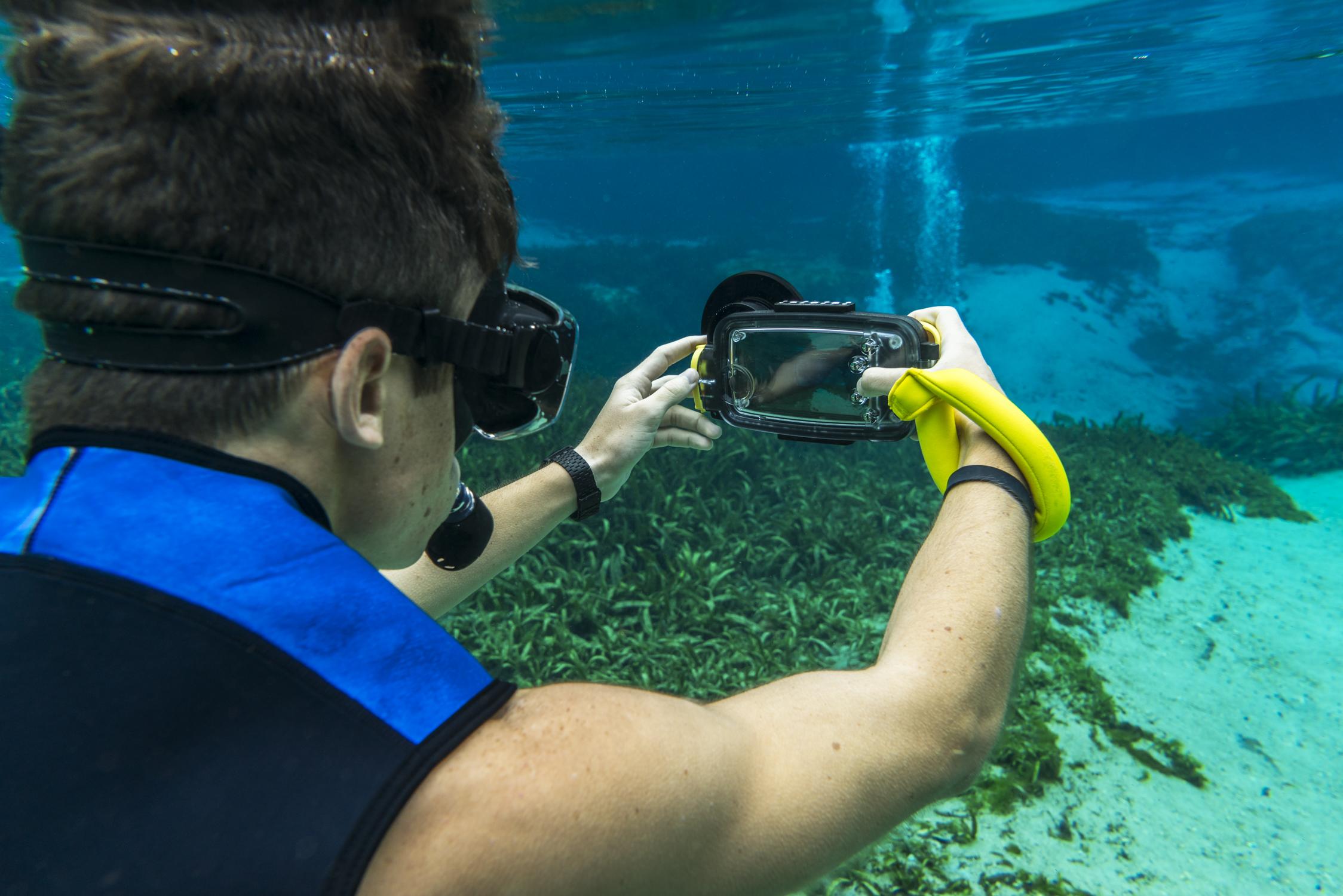 A snorkeler using a smartphone camera underwater