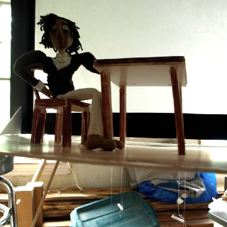Gregory, the main character, seated in front of the shadow screen. Visible beneath the deck (and running through the legs of the table) are the controls for his left hand