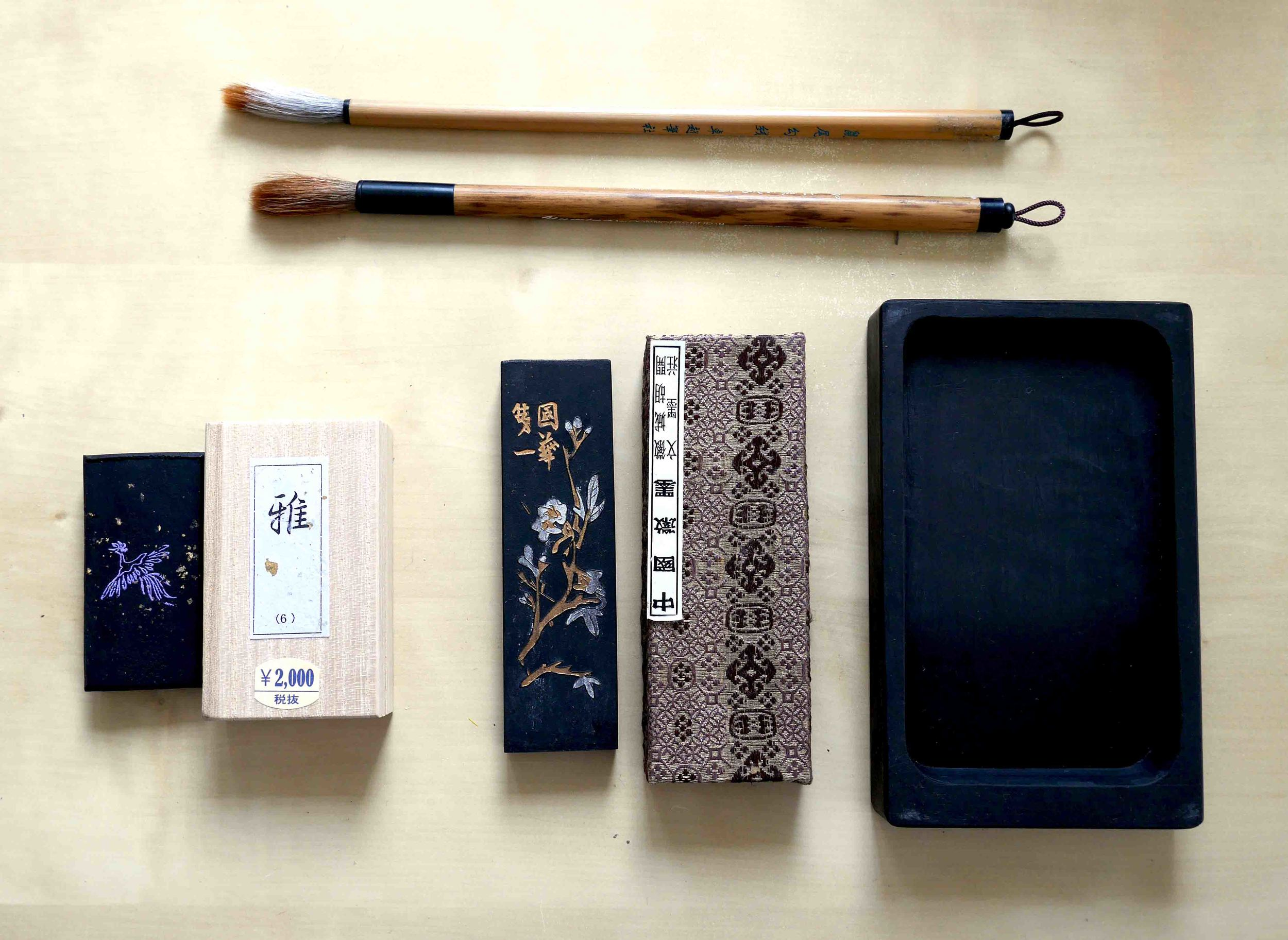 Tools of the trade: beautifully embossed ink sticks, a simple ink stone, and bamboo brushes.