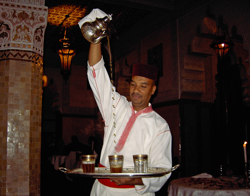 This server is creating a foamy top by pouring the tea from up high!