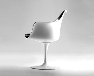 SA05: 1958  |                                      Eero Saarinen                  Pedestal swivelarmchair with black or white bright lacquered cast aluminium base. Seat and back in resin. Cushion in expanded foam covered with fabric or leather.