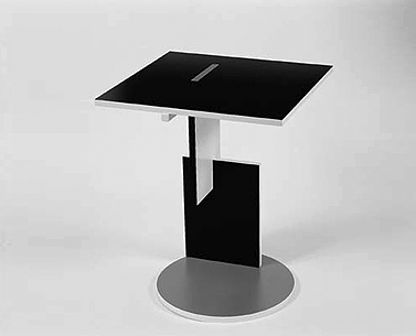 RI09:  1918-23  |                                      Gerrit Thomas Rietveld                 Small table with base and top in red, white, black, blue and yellow lacquered plywood.   This table is one of the furnishings characterizing the interior of the best-known building designed by Rietveld, the Schröder house built in Utrecht in 1924.