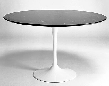 SA69-1: 1956  |                                      Eero Saarinen                                      Table: base in cast aluminium black or white lacquered, bright or matt. Top diameter cm. 120 in a variety of finishes.