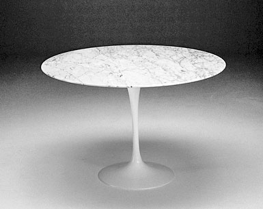 SA69-5: 1956  |                                      Eero Saarinen                                      Table: base in cast aluminium black or white lacquered, bright or matt. Top diameter cm. 90 in a variety of finishes.