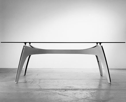 XSPIDER:  1997  |                                       Massimo Imparato                                      Ranieri  Massola                                       Table with structure made of two pairedoff steel sheets available in the following finishes:A) Black or aluminium lacquered base B) Various colors lacquered base C) Grinded and lacquered with a transparent finish base.Available with rectangular orshaped glasstop 15 or 19 mm thick.