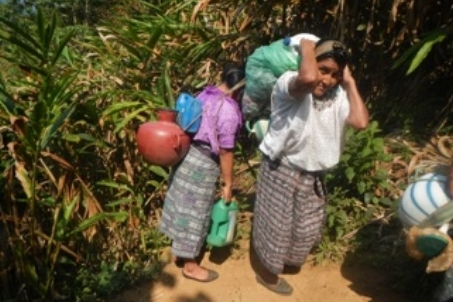 Villagers trekking back up the mountain with water from the spring