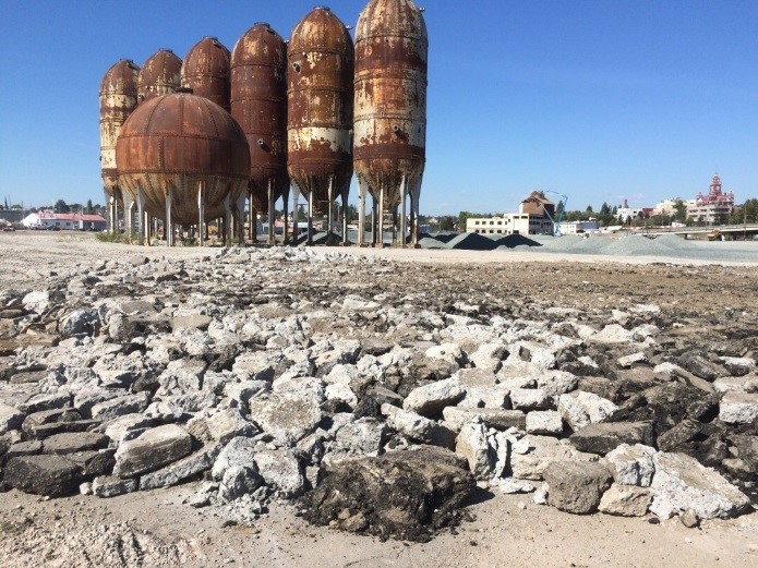 """Crushed concrete from mill demolition. Also note that the Port saved some buildings and structures, like the """"acid ball"""" and the """"pulp digester"""" towers shown here, to contribute to the aesthetics of the planned redevelopment."""