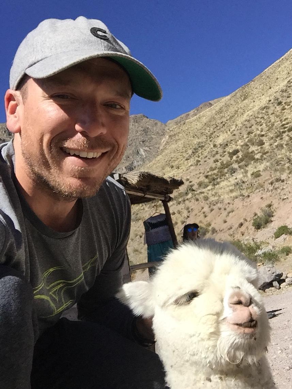 Chad and baby llama in Colca Canyon, Peru.