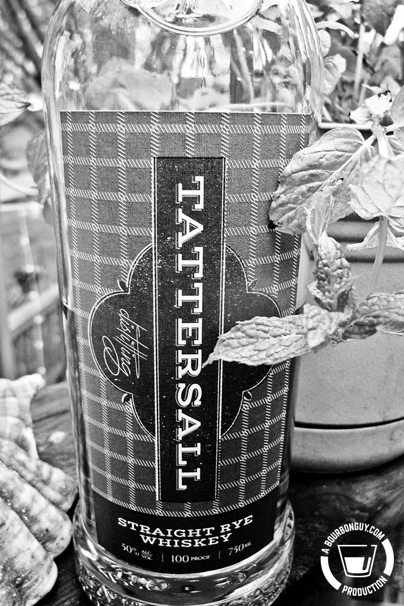 Image: a bottle of Tattersall Straight Rye Whiskey nest to a mint plant