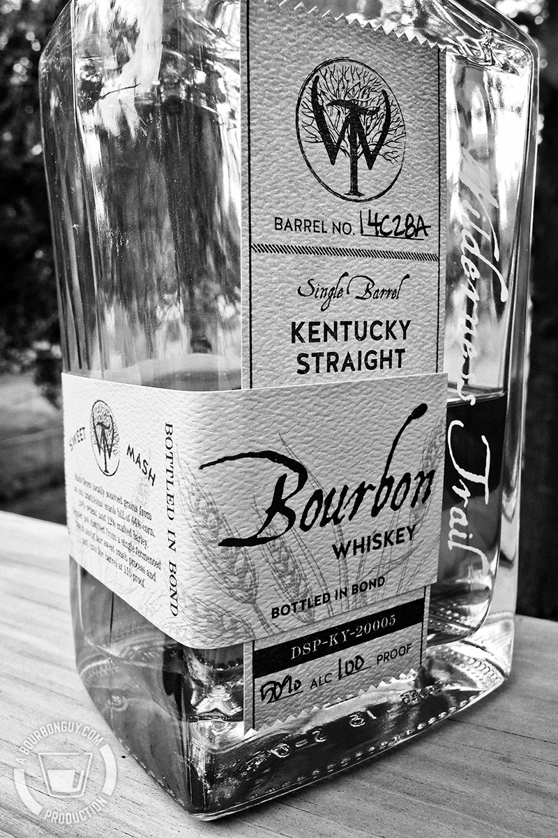Image: a three quarter view of the Wilderness Trail Bottled-in-Bond Bourbon bottle showing that it is Bottled in Bond, non-chill filtered and made from a sweet massh process.