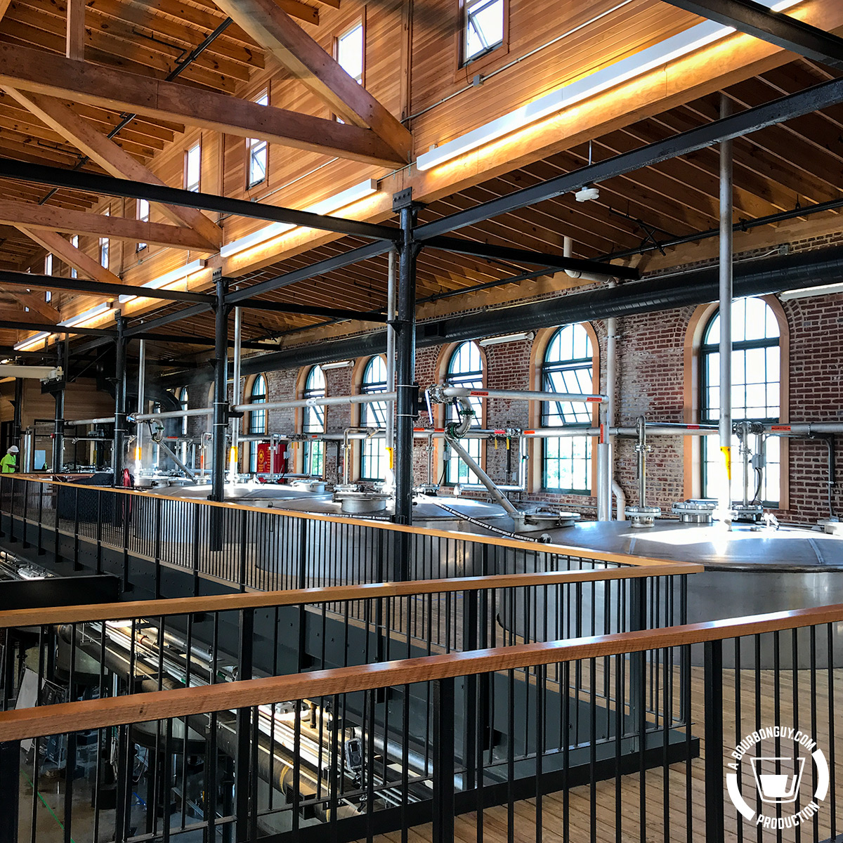 IMAGE: The Angel's Envy Distillery Fermenters. Wood and metal railings with closed fermenters in the background