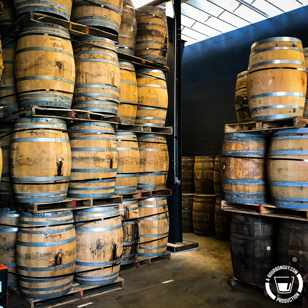IMAGE: Angel's Envy Barrel Finishing room. Barrels are stacked on end and are on pallets.
