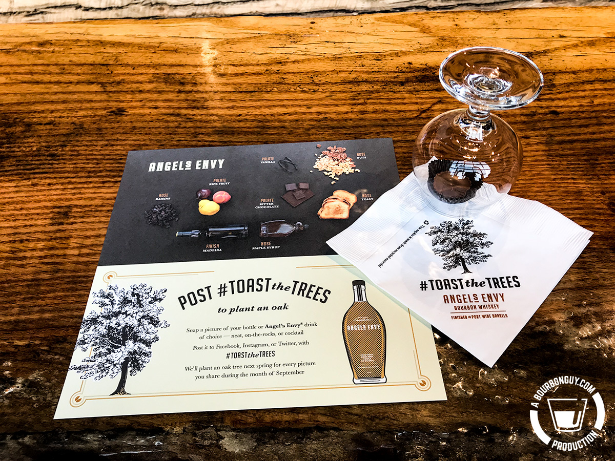 IMAGE: A glass, a napkin, and a printed card displayed as part of a tasting. The hashtag #ToastTheTrees is displayed prominently.