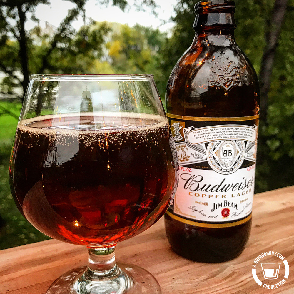 IMAGE: a glass of Budweiser Copper Lager. Rich copper color in a tulip style beer glass. Behind it is a bottle of the beer.