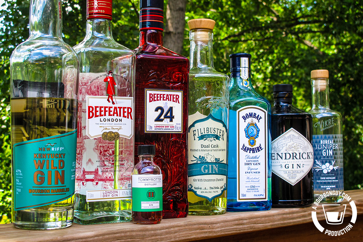 IMAGE: A gin lineup consisting of: New Riff Kentucky Wild Gin, Beefeater London Dry Gin, Beefeater 24 London Dry Gin, Tommyrotter Cask Strength Bourbon Barrel Gin, Filibuster Dual Cask Gin, Bombay Sapphire London Dry Gin, Hendrick's Gin, and Vikre Boreal Juniper Gin.