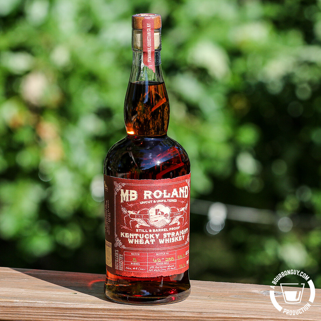 IMAGE: A bottle of MB Roland Wheat whiskey sitting on a railing in the morning sunlight.
