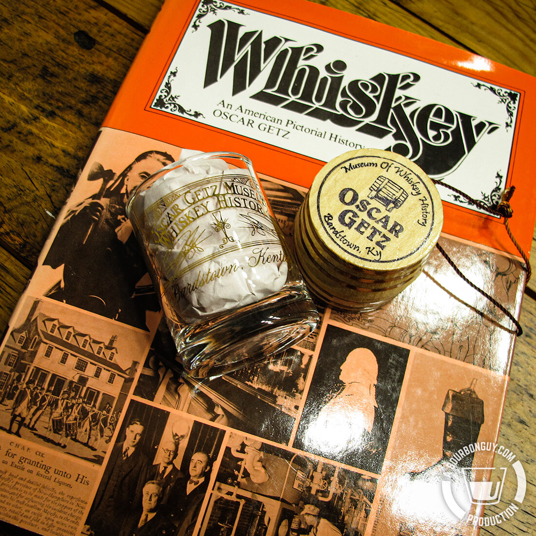 IMAGE: The book  Whiskey: An American Pictorial History  by Oscar Getz, an Oscar Getz Museum Shot Glass and an Oscar Getz Museum Ornament.