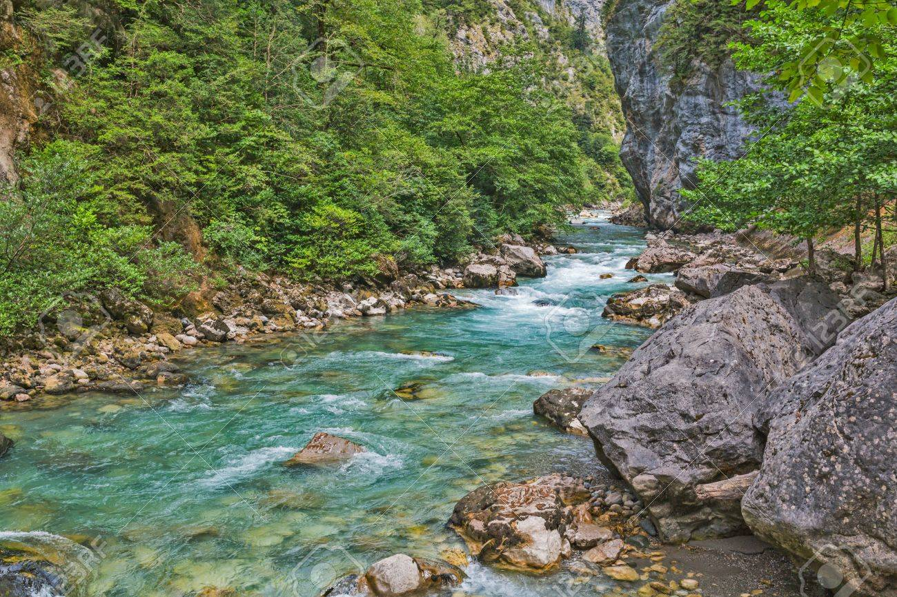 45792324-mountain-river-flowing-by-the-gorge-with-rocks-and-trees.jpg