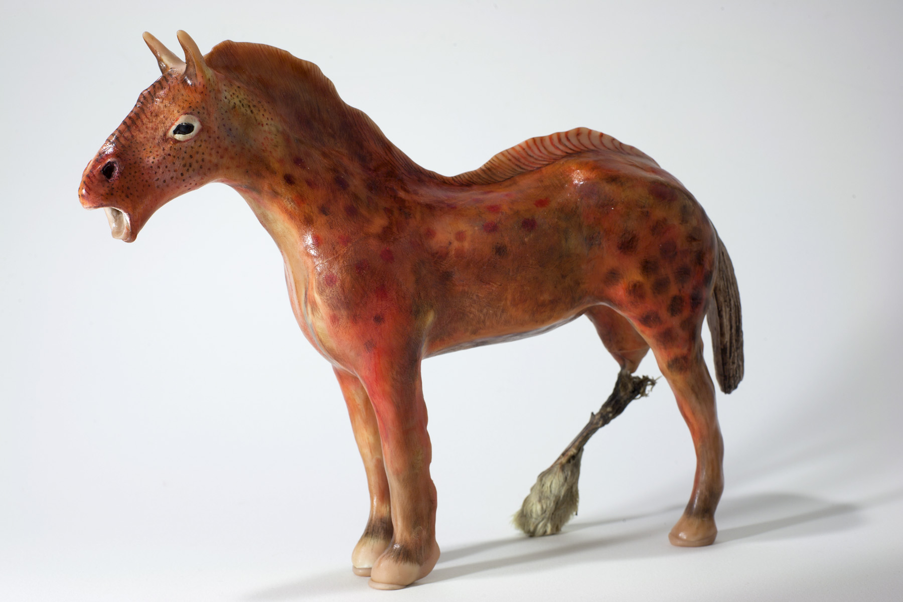 "Rabbit Foot Red, 2014, Mixed Media altered plastic toy horse, clay, colour pencil crayons, rabbit foot, 3"" x 9"" x 11"""