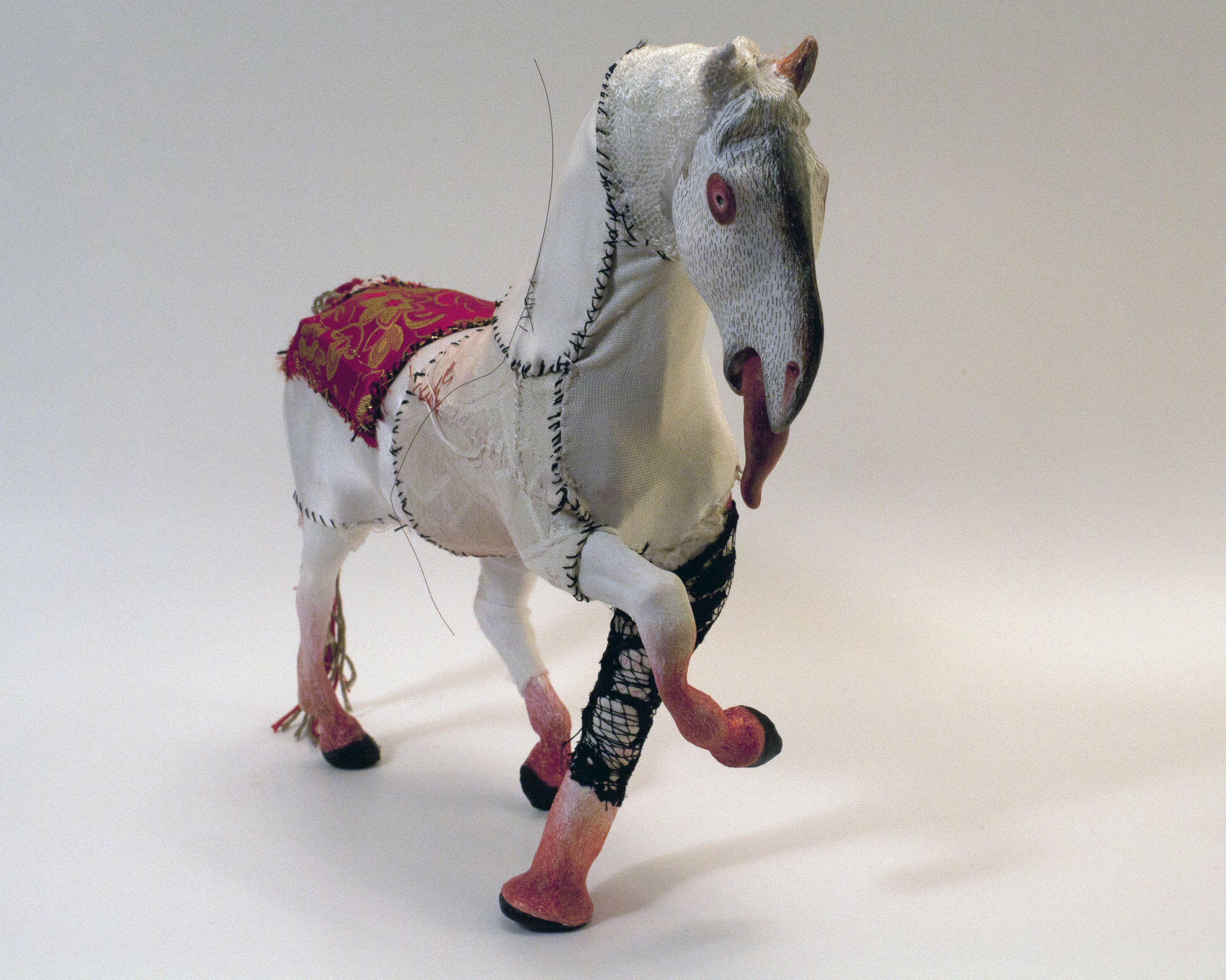 "Horse with Red Eyes, 2012, Mixed Media altered plastic toy horse, fabric, thread, clay, gesso, horse hair, embroidery thread, colour pencil crayons, 3.25"" x 8.5"" x 11"""