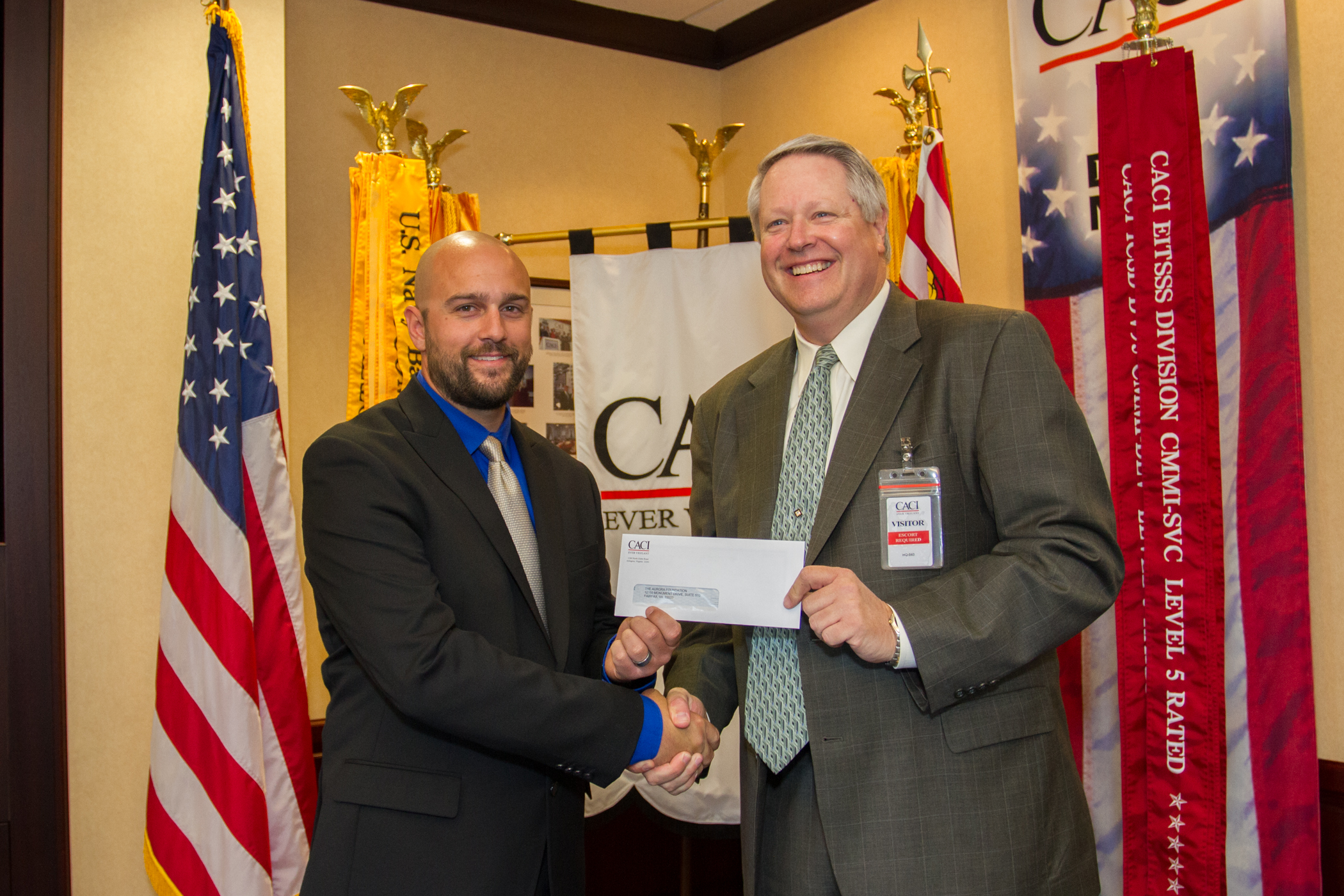 Josh Tredinnick (Left), US Army Veteran and CACI employee, presents Tom DeWitt, Aurora Foundation Founder, with a donation from CACI in June 2014.
