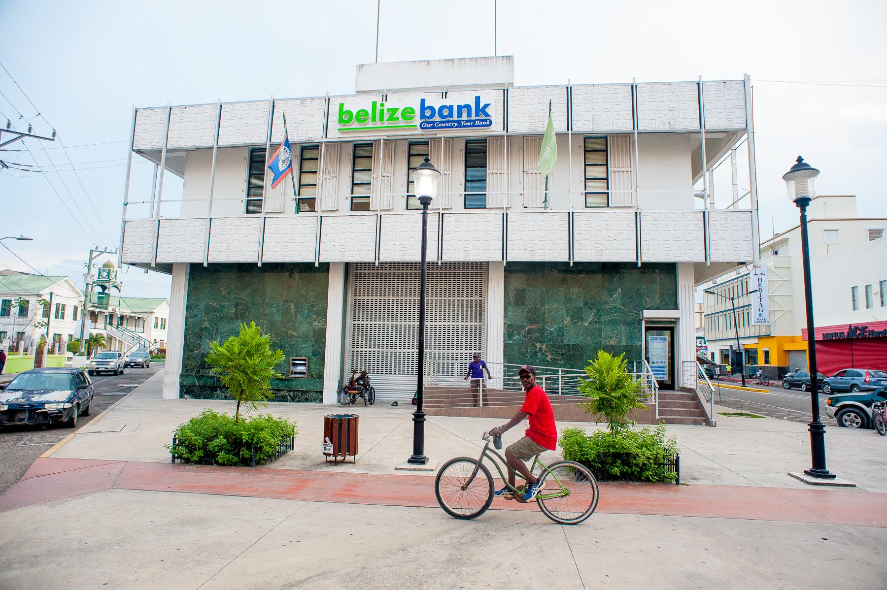 CAPTION:A cyclist rides past Belize Bank in downtown Belize City, April 23, 2017. Photo courtesy Caribbean Network Operators Group.