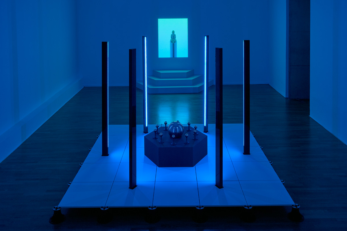 ////  ROOM 01 - A precision CNC platform on pedestals, with custom fabricated aluminium LED light columns, and CNC routed table with Jesmonite holders and spheres. The rear artwork is an an illusionary light installation that appears as a projection, consisting of a 3d printed an Jesmonite cast Buddha statue installed into a temporary gallery wall and backlit with LEDs.