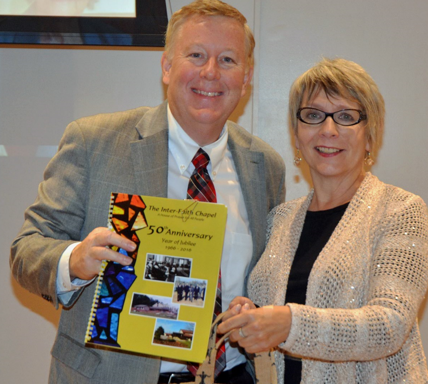 Dr. rea presents the first copy of the 50th anniversary booklet to Arlene Kaiser who did the layout.