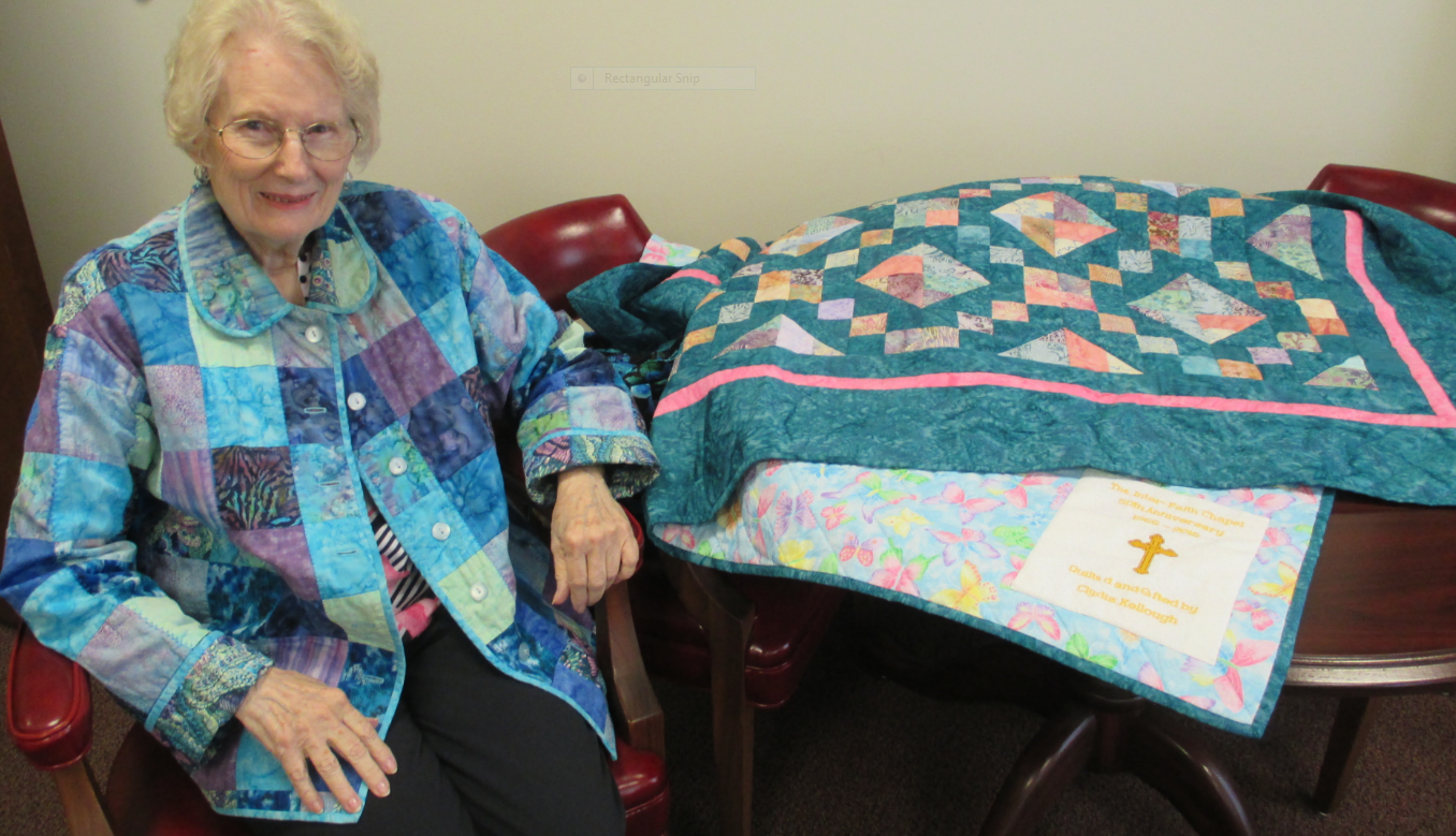 Clydis Kellough and the quilt she donated to the chapel to raise funds.
