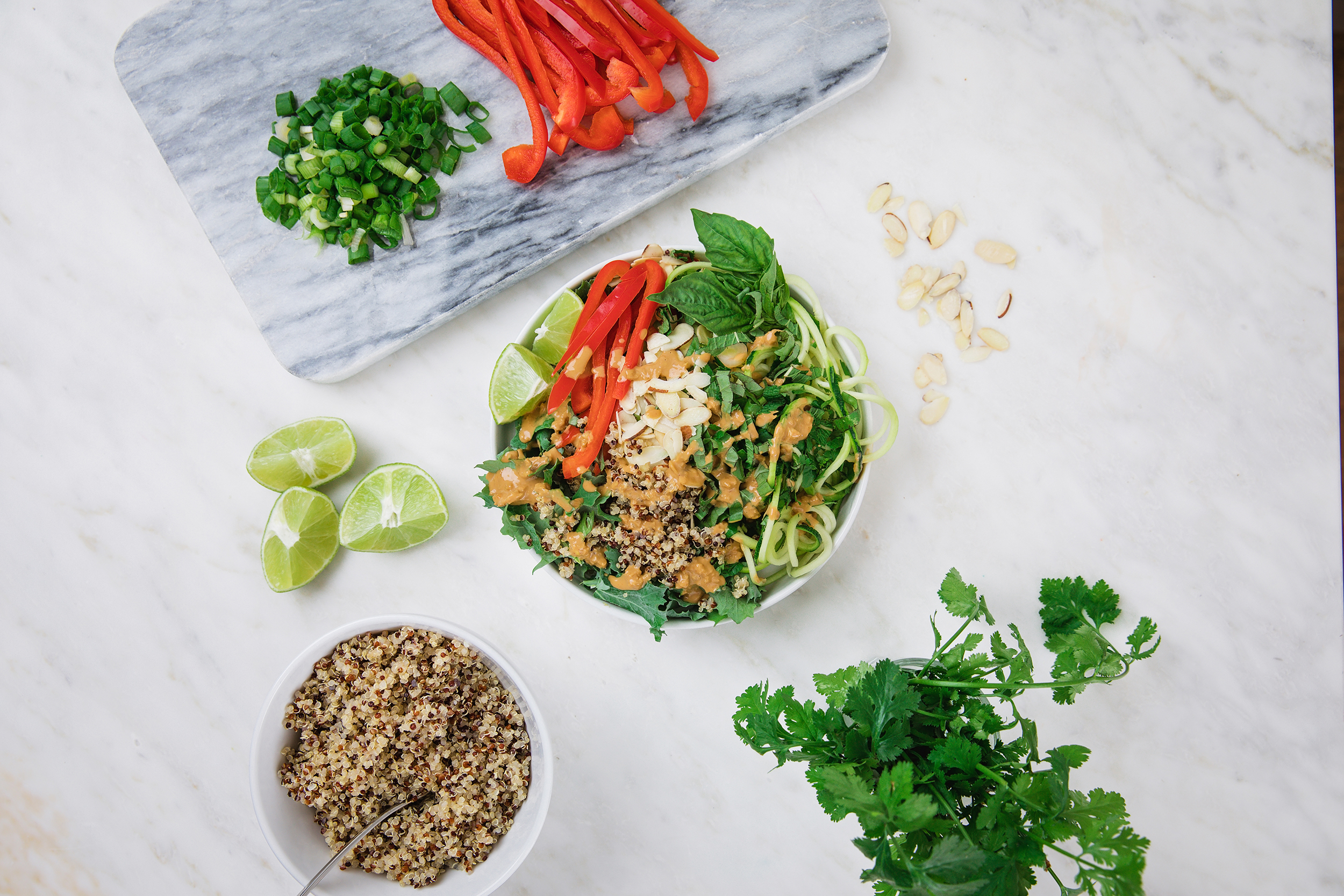 Flat view look at the Thai Summer Roll Salad with zucchini, kale, quinoa, almonds and 1 red bell pepper.