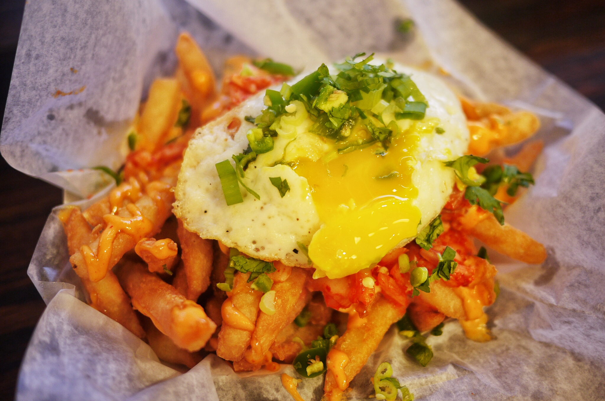 Loaded Kimchi Fries $5.99.  Seasoned and battered French fries topped with mild spicy mayo, mild kimchi, chopped scallions, cilantro and jalapenos, and then topped with fried runny egg. HELL YEAH THIS THING IS GOOD!The portion is enough for sharing up to 3 people, so worth the price.