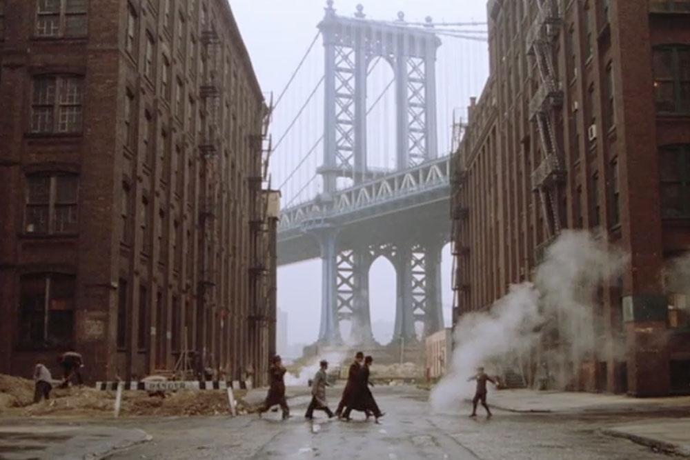 """Bildquelle:  http://dumbonyc.com/blog/2016/02/09/dumbo-brooklyn-film-tv-locations/   Berühmt geworden durch eine Einstellung in Sergio Leones Gangster-Epos """"Once upon a time in America"""" (1984, siehe oben), ist dieser Blick auf die Manhattan Bridge in Brooklyn heute eines der meist fotografierten Motive in New York und Beispiel dafür, wie bestimmte Darstellungsweisen eines Objektes über die Jahrzehnte hinweg immer wieder aufgegriffen werden und so den eigenen Blick """"manipulieren"""" können."""
