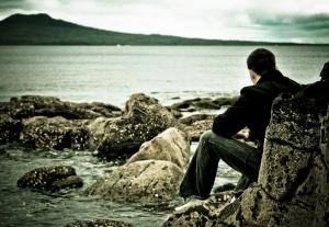 homem-sentado-em-pedras-junto-ao-mar-olhando-para-extensao-das-aguas.jpg