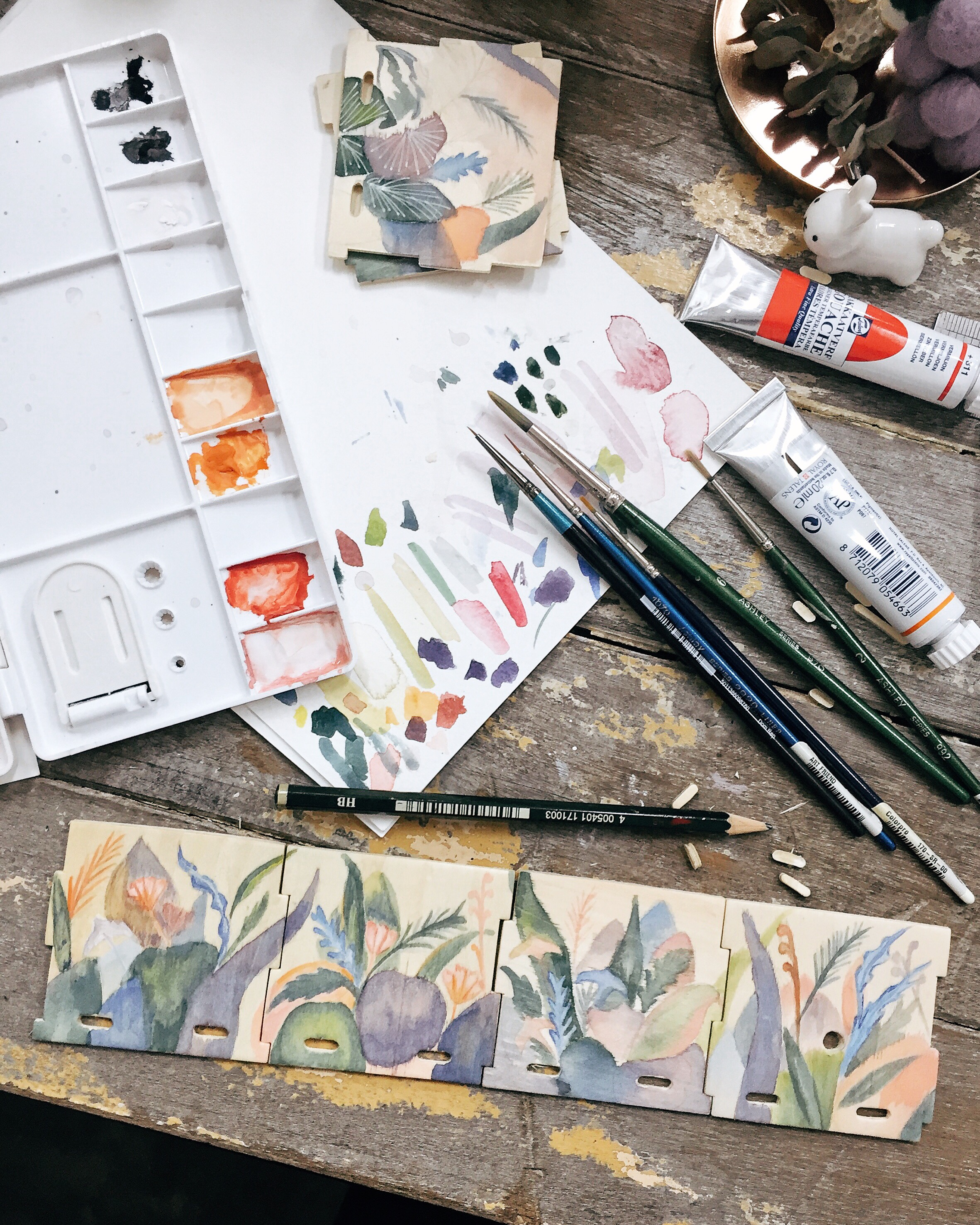 A rare photo of my messy work desk – experimenting with gouache on wood.