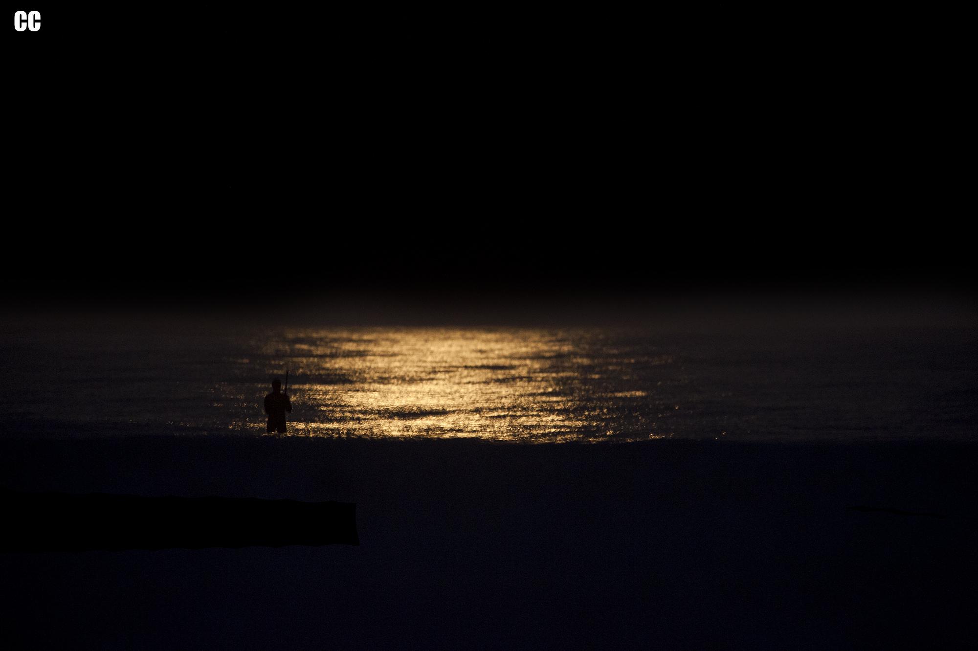 Lonely Fisherman using the full moons light.