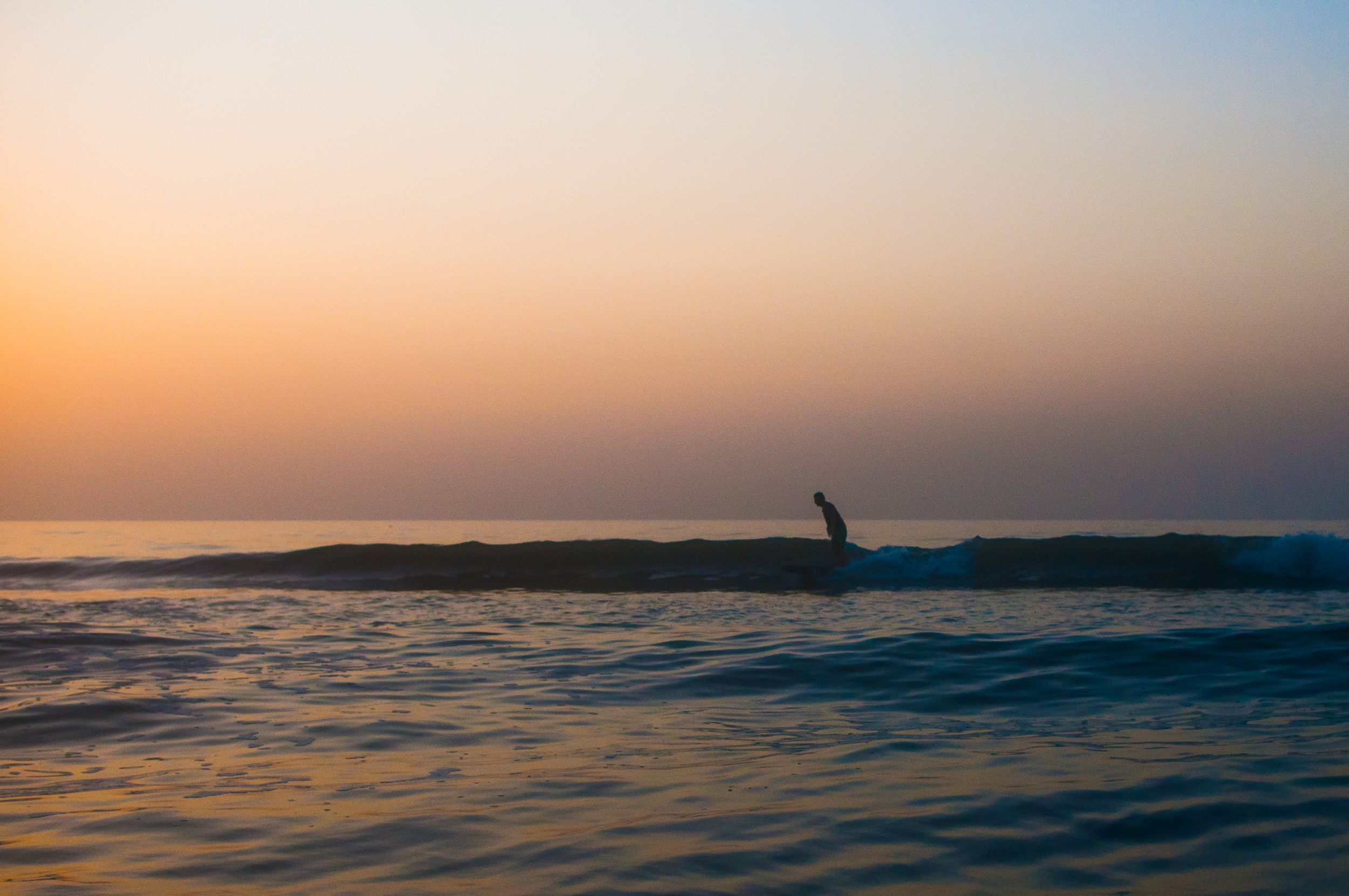 This was Chris's first wave of the morning. I was just dialing in the setting on my housing in knee deep water and he takes off on this long right. The sun was still below the horizon and the wind was dead. One of my favorites from the session.
