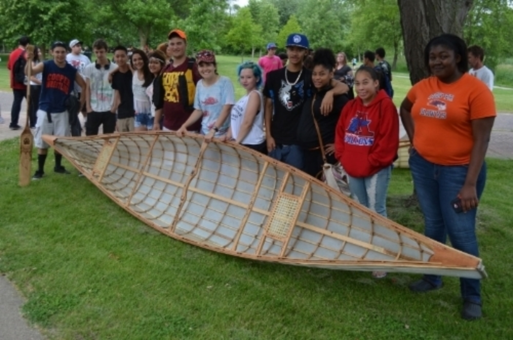 Proud students show off one of the canoes.