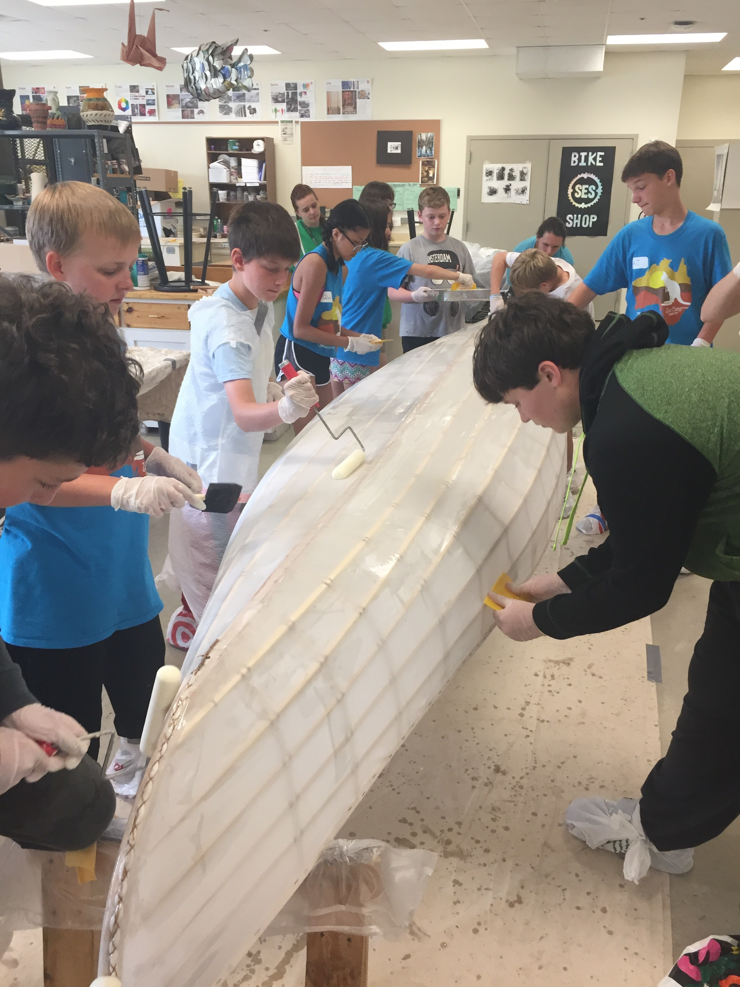 Students at the MN Zoo work together to build a canoe in an intensive two week program.