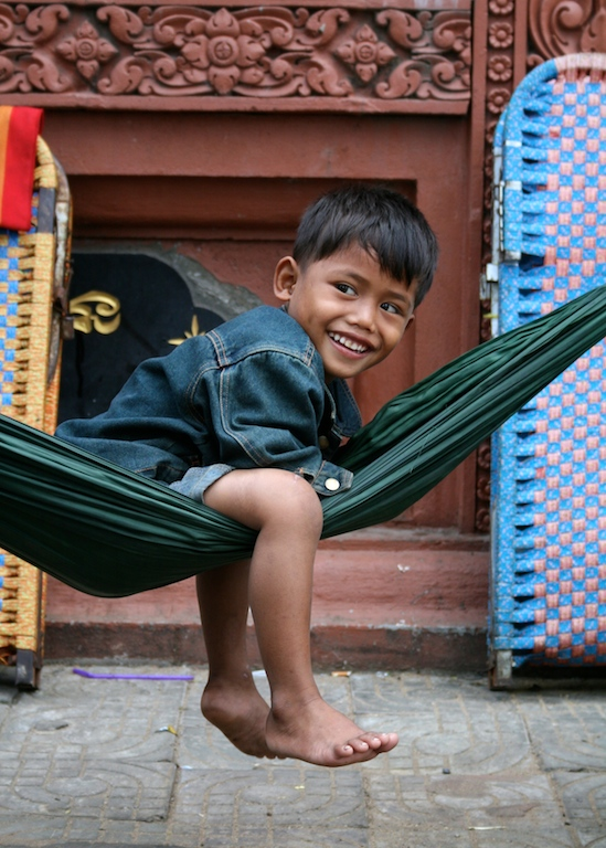 Child swings in a hammock outside Wat Phnom, Phnom Penh