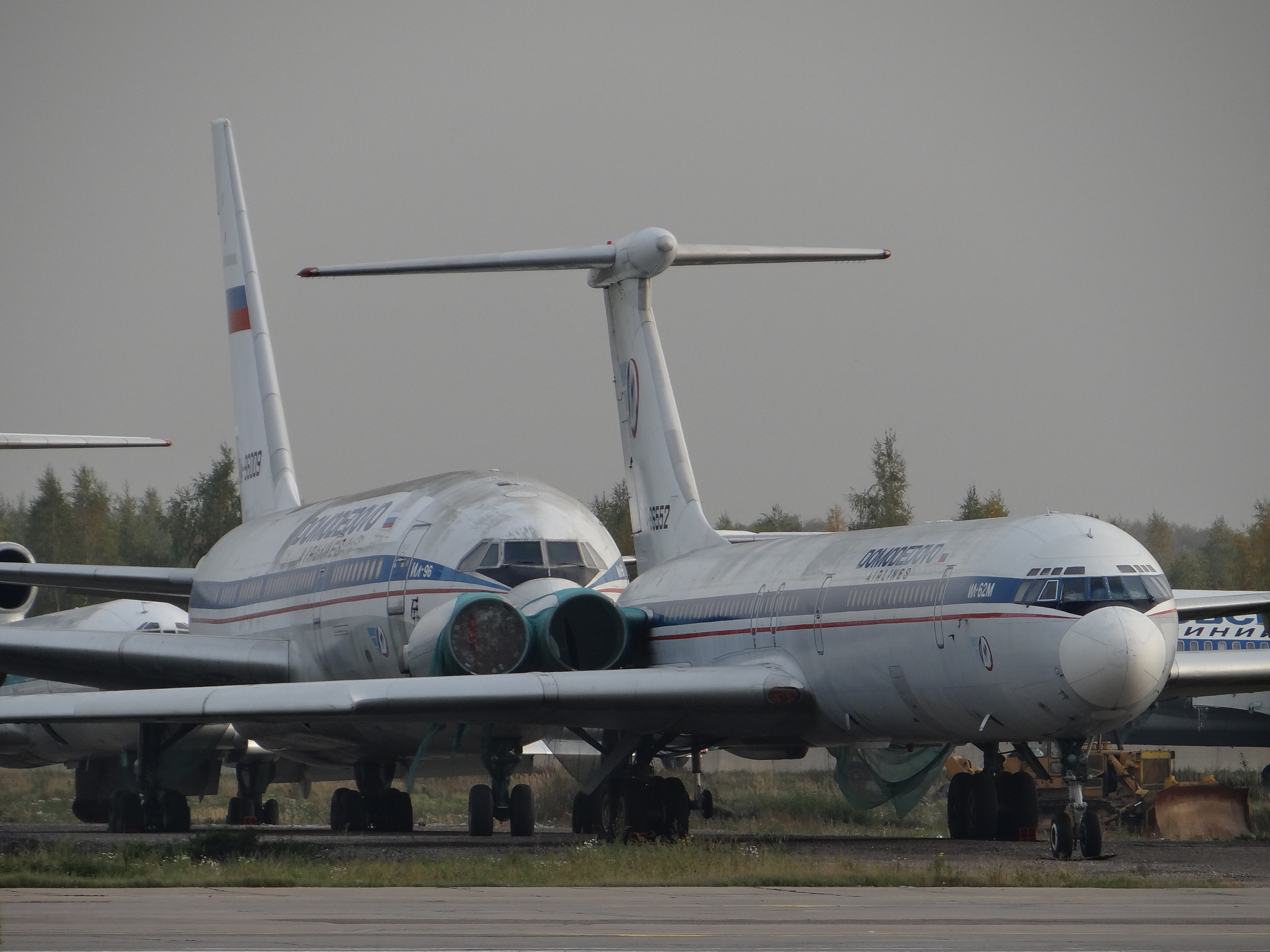 A bit of Russian/Soviet aviation archaeology at DME: an Ilyushin Il-96-300 and a Il-62M of the late  Domodedovo Airlines , a carrier that ceased operations in 2008. Still quite an impressive sight.
