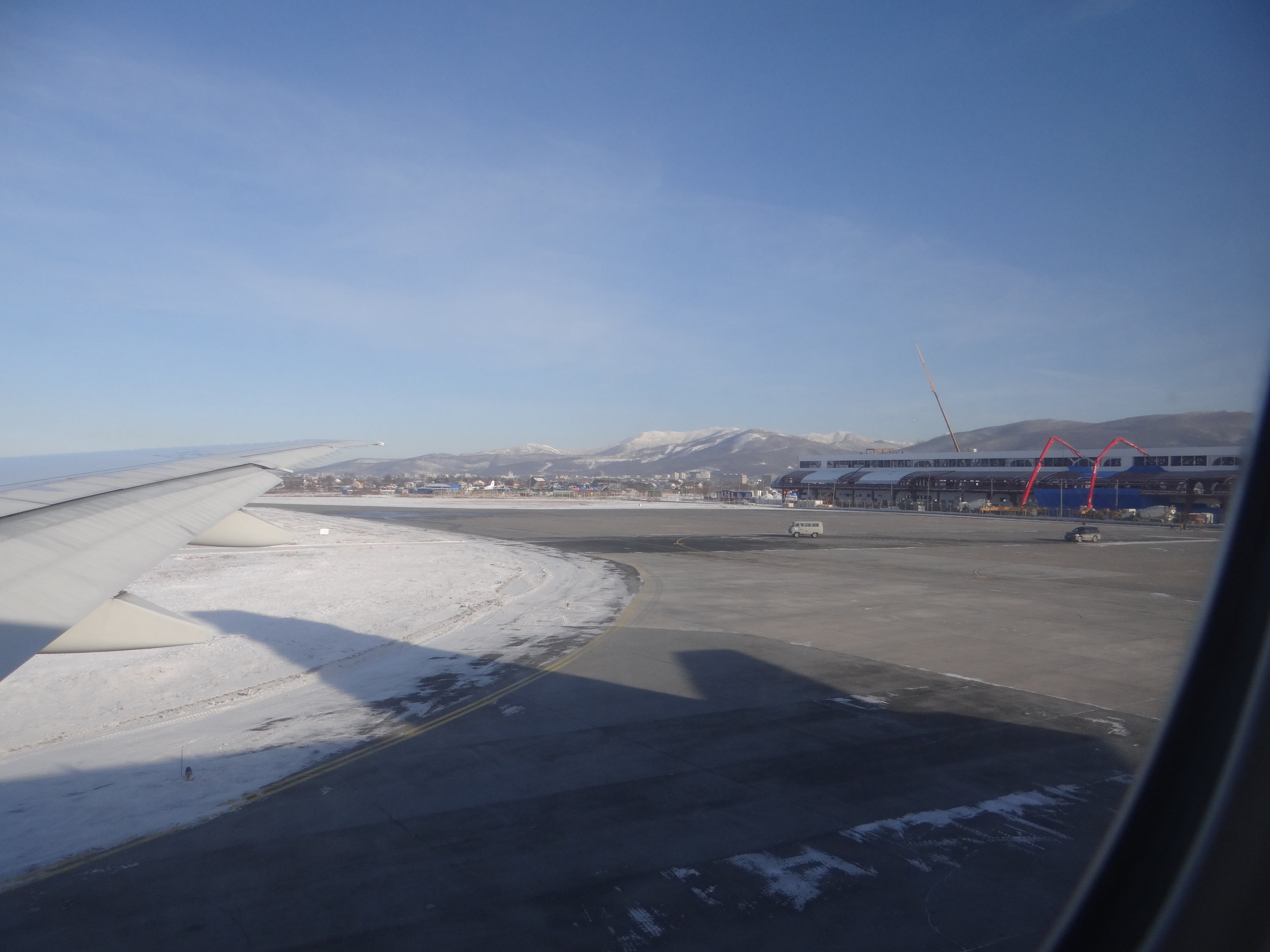 Window view of Yuzhno-Sakhalinsk airport, with the new terminal, under construction, clearly visible