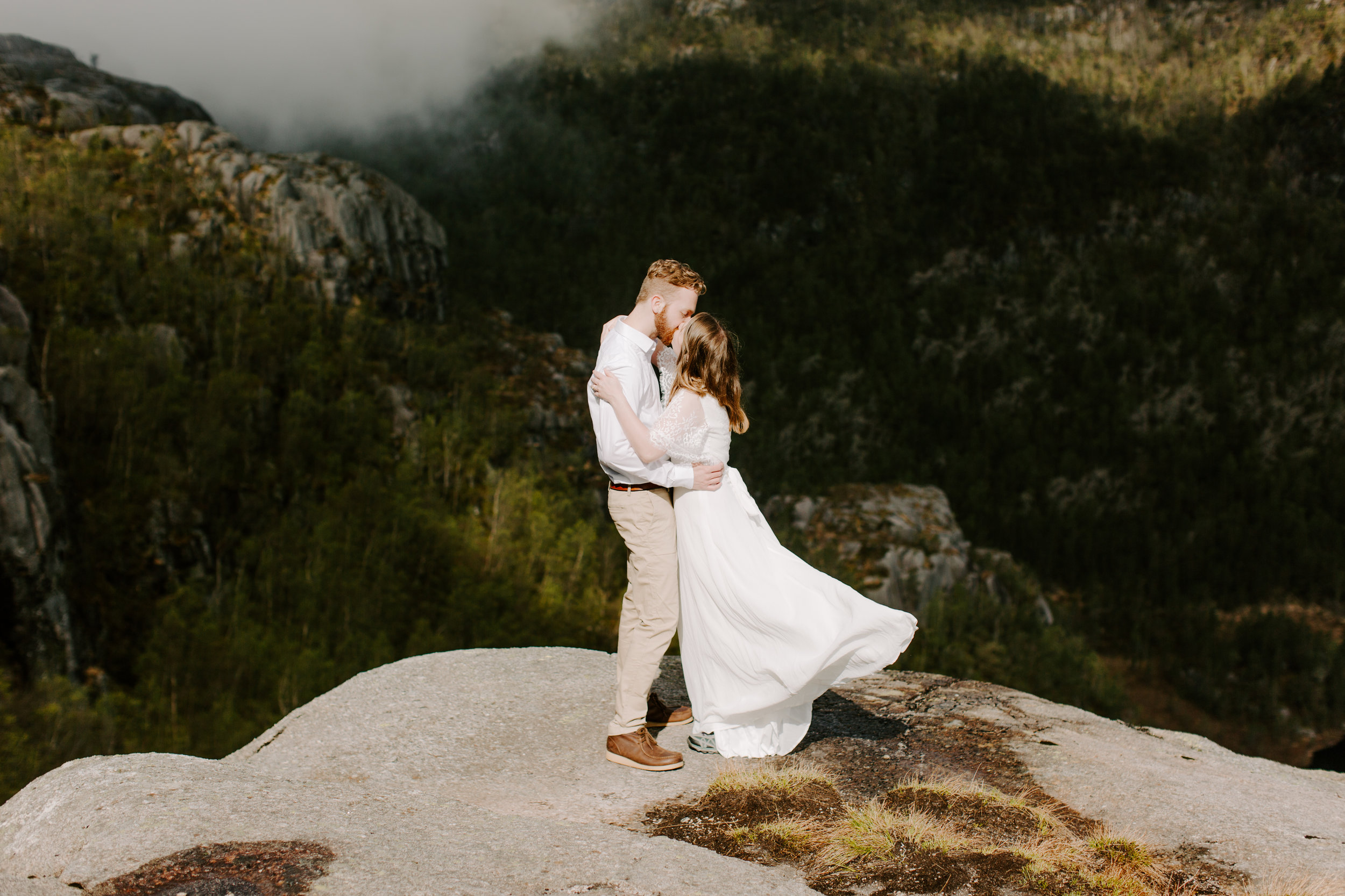 bride and groom kissing on cliff in the wind