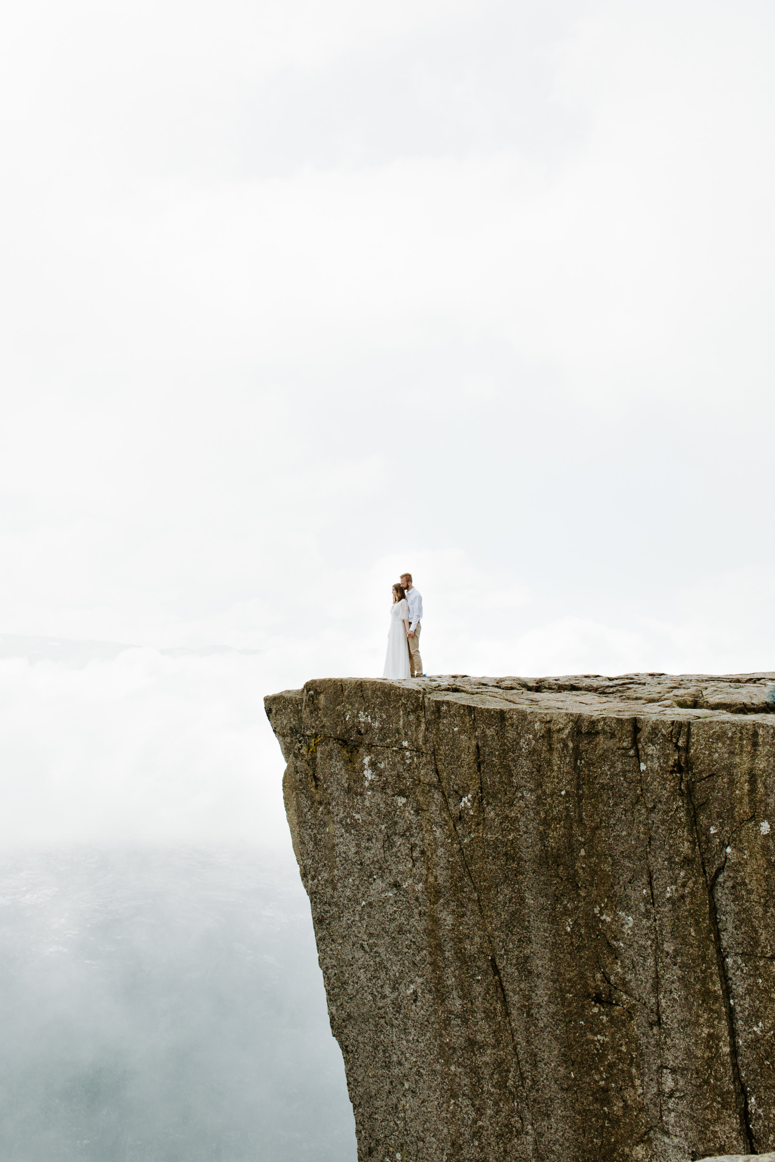 bride and groom on cliff pulpit rock