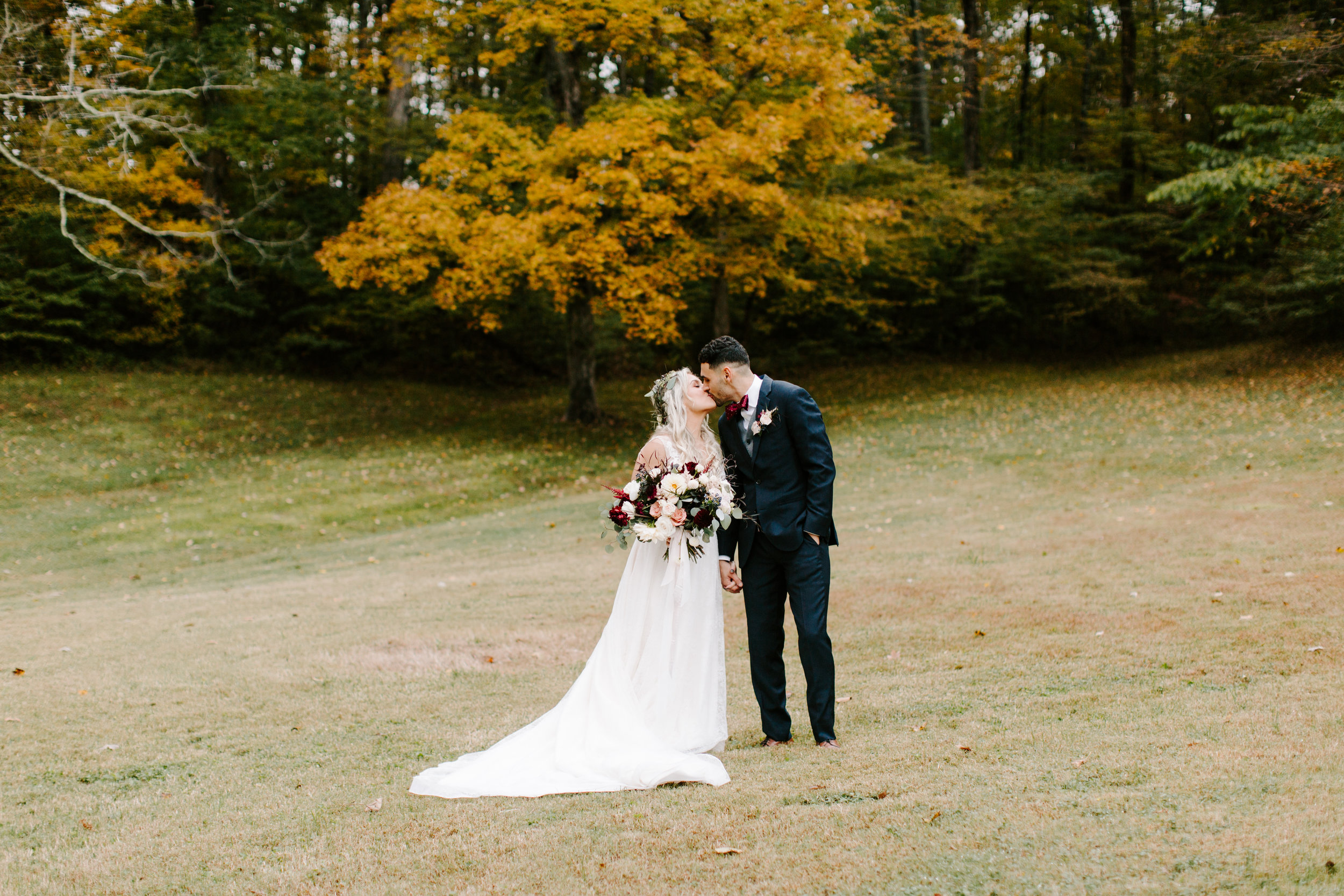 bride and groom kissing in the fall